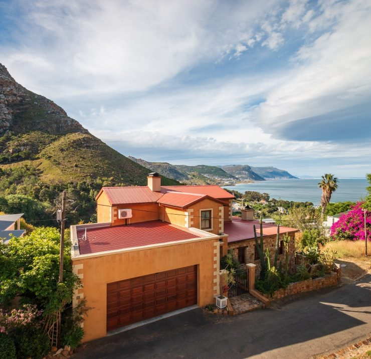 Scenic view over houses in Simon's Town to False Bay and Kalk Bay against blue sky with clouds