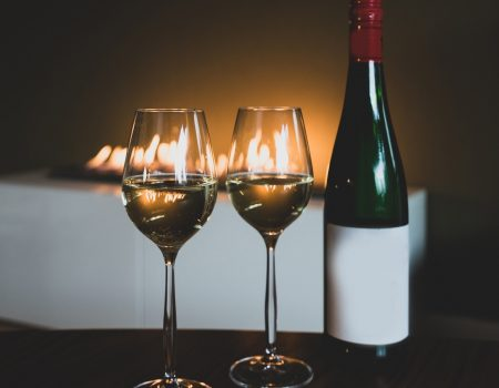 Two glass of white wine and bottle near a fireplace
