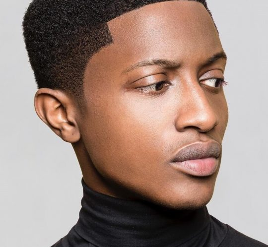 A young man wearing his natural hair well groomed man